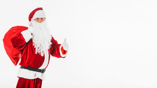 Santa claus with big sack showing thumb up gesture Free Photo