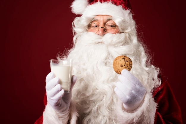 Babbo natale con un biscotto e un bicchiere di latte Foto Gratuite