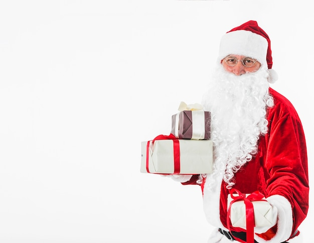 Santa claus with gift boxes in hands Free Photo