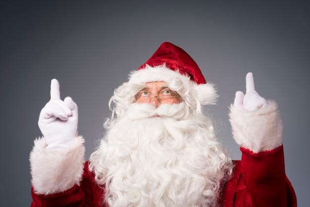 위쪽 방향을 보여주는 손으로 산타 클로스 무료 사진