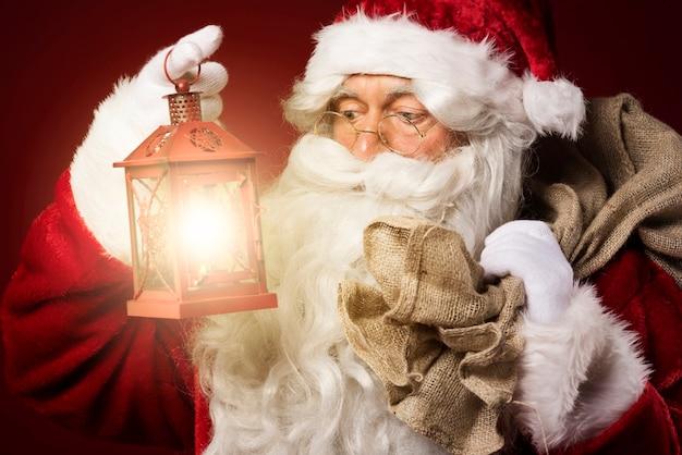 Babbo natale con una lanterna e un sacco di regali Foto Gratuite