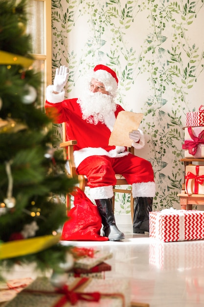 Santa claus with letter sitting on chair Free Photo