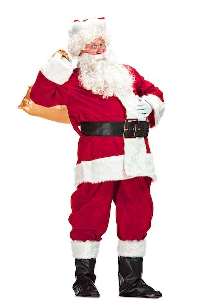 Babbo natale con una lussuosa barba bianca, cappello di babbo natale e un costume rosso isolato su uno sfondo bianco con doni Foto Gratuite