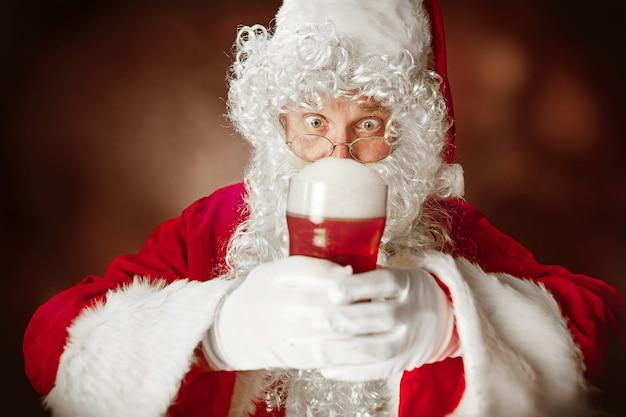 Babbo natale con una lussuosa barba bianca, cappello di babbo natale e un costume rosso Foto Gratuite