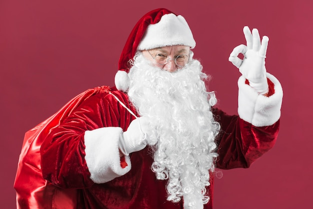 Santa claus with sack showing okay gesture Free Photo