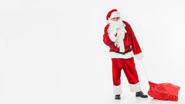 Santa claus with sack showing secret gesture Free Photo