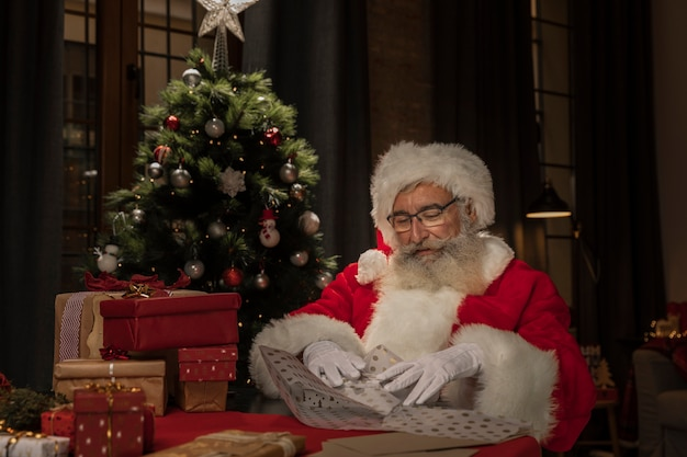 Santa claus wrapping up presents Free Photo