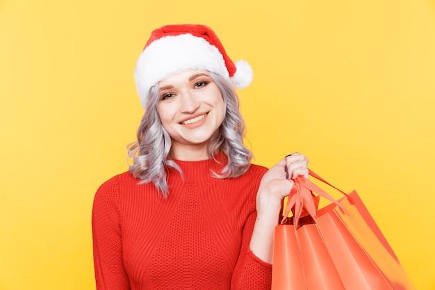 노란색 방에 고립 된 선물 큰 가방을 들고 모자에 산타 소녀. 프리미엄 사진