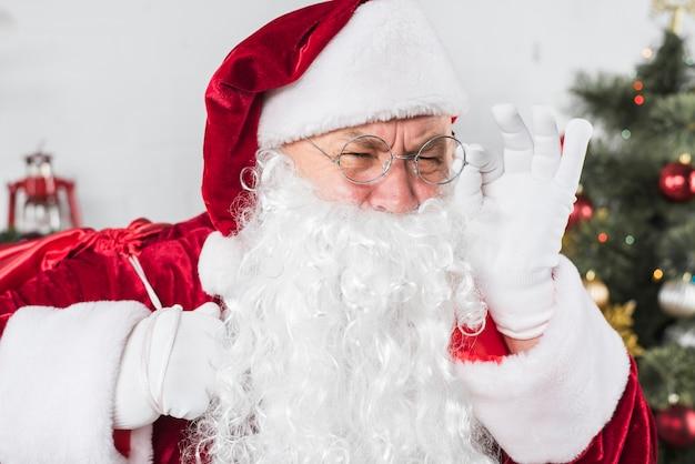 Santa in vetri vicino all'albero di natale decorato Foto Gratuite