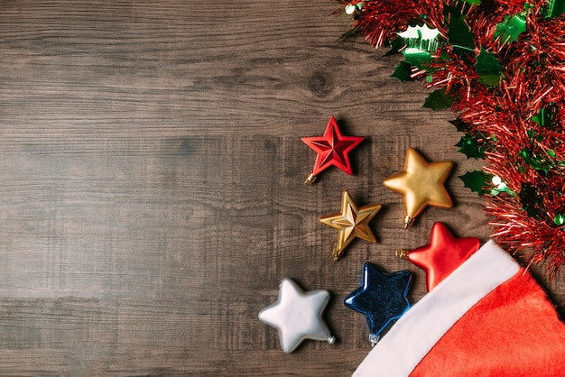 Santa hat with metallic stars and ornament on wooden background. Premium Photo