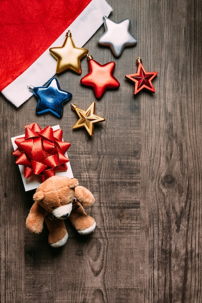 Santa hat with metallic stars, present and teddy bear on wooden background. Premium Photo