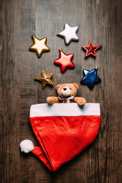 Santa hat with teddy bear inside and metallic stars on wooden background. Premium Photo