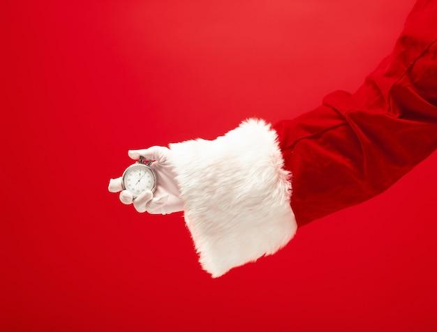 Санта держит секундомер на красном фоне. сезон, зима, праздник, праздник, концепция подарка Бесплатные Фотографии