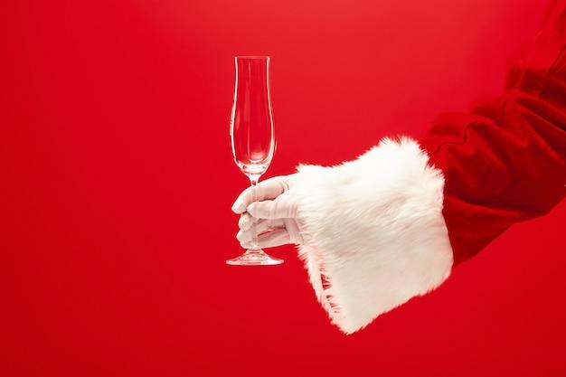 Bicchiere da vino santa holding champagne su sfondo rosso. stagione, inverno, vacanza, celebrazione, concetto di regalo Foto Gratuite