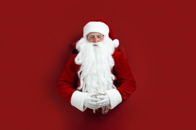 종이에 구멍을 통해 명상 산타 남자입니다. 프리미엄 사진