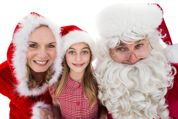 Santa and mrs claus smiling at camera with little girl Premium Photo