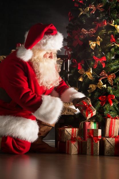 Санта кладет подарки под елку в темной комнате Premium Фотографии