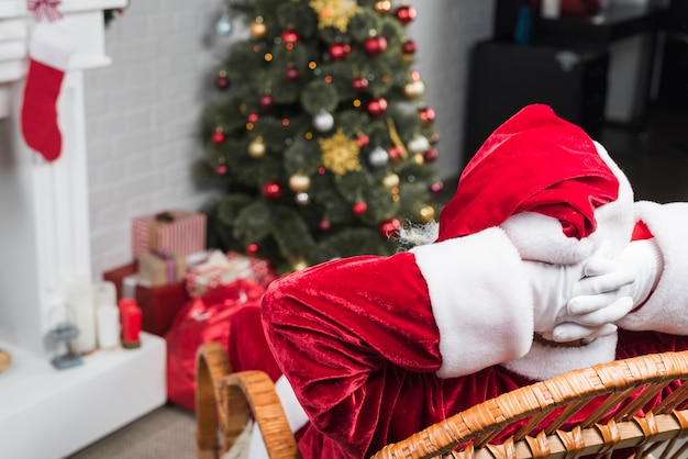 Santa sitting on rocking chair with hands behind head Free Photo