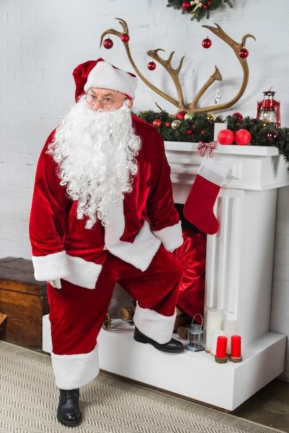 Santa in piedi vicino al camino bianco Foto Gratuite