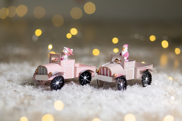 Santa statuette rides on a toy car with a trailer for gifts  festive decor, warm bokeh lights. Premium Photo