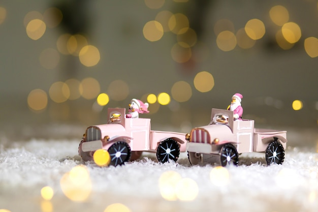 Santa statuette rides on a toy car with a trailer for gifts Premium Photo
