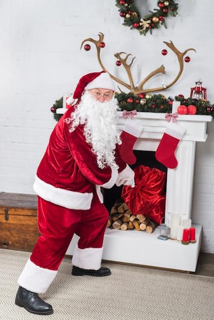 Santa con il grande sacco di entrare in casa Foto Gratuite