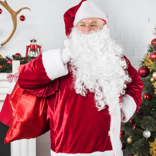 Santa con grande sacco vicino albero di natale Foto Gratuite