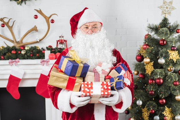 Santa with gift boxes in hands near christmas tree Free Photo