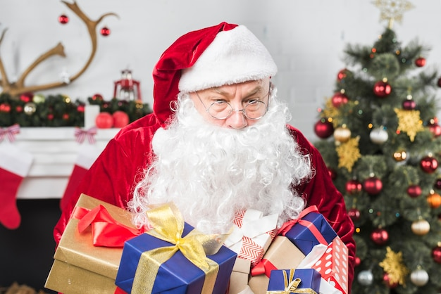santa with gift boxes near decorated christmas tree free photo