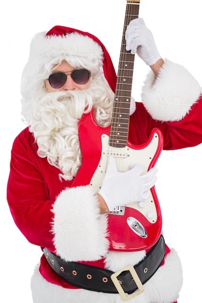 Santa with sunglasses playing electric guitar Premium Photo