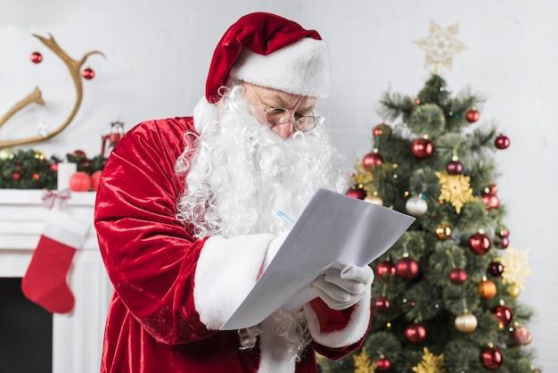 Santa scrivendo su carta vicino albero di natale decorato Foto Gratuite