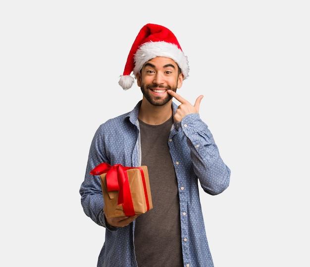 若い、身に着けていること、santa、帽子、笑顔、ポインティング Premium写真