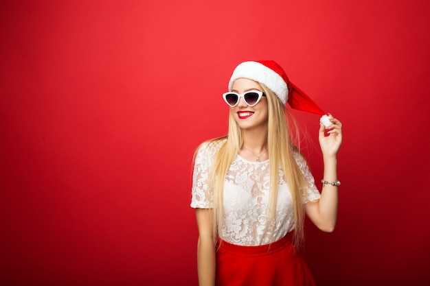 Задумчивая блондинка в шляпе santa на красной изолированной предпосылке. солнцезащитные очки в белой оправе. Premium Фотографии
