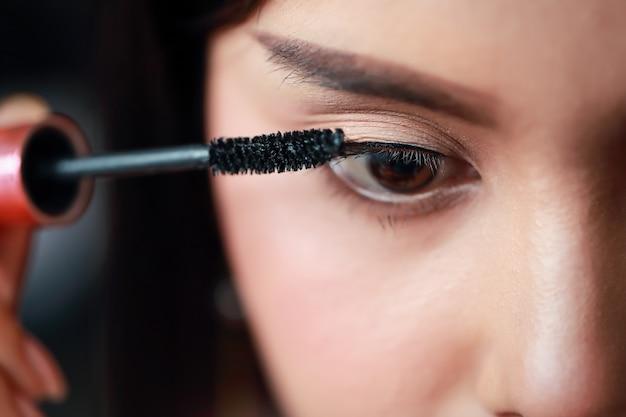 Молодая азиатская девушка santa прикладывая тени глаза на красивом лице Premium Фотографии
