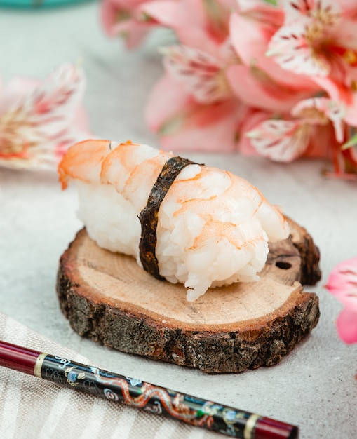 Sashimi roll on a piece of wood. Free Photo