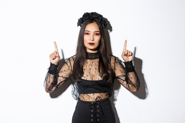 Sassy beautiful asian woman in black gothic dress, wearing witch costume for halloween and pointing fingers up, showing your logo or banner on empty white background, white background. Free Photo
