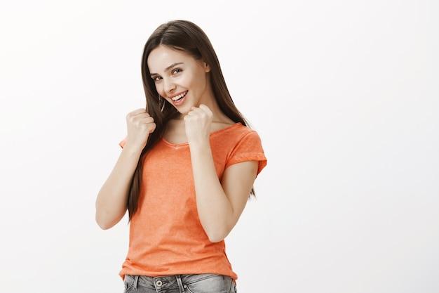 Sfacciata e civettuola bella ragazza shadowboxing, alzando le mani come un pugile Foto Gratuite