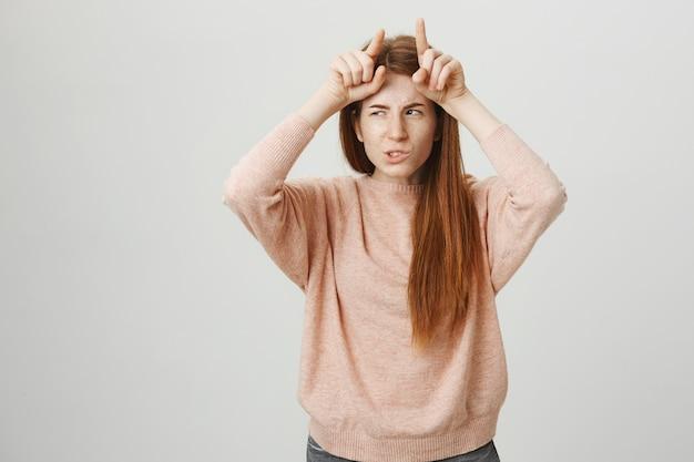頭に悪魔の角を示す生意気なかわいい赤毛の女の子 無料写真