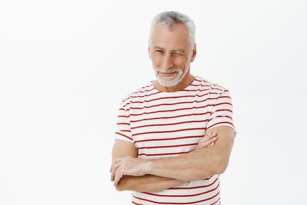 Uomo anziano bello impertinente che sbatte le palpebre incoraggiante Foto Gratuite