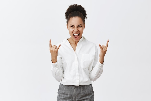Sassy successful african american businesswoman showing rock-n-roll gesture, winning or triumphing Free Photo