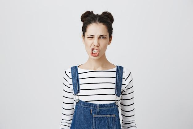 La giovane donna impertinente stringe i denti, facendo smorfie Foto Gratuite