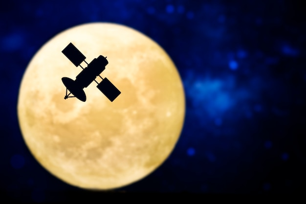 Satellite silhouette over a full moon Free Photo