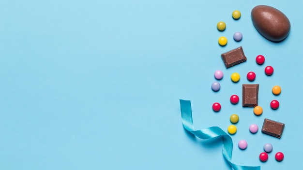 Satin ribbon; gem candies and easter eggs with space for writing the text on blue backdrop Free Photo