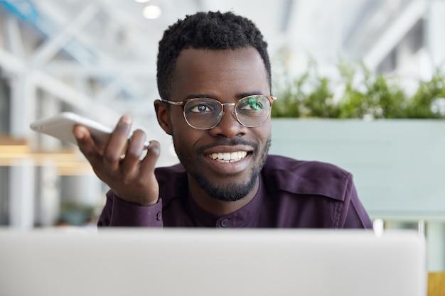 満足しているアフリカの男性受付係は、スマートフォン経由でクライアントに情報を送信し、高速インターネットを使用します。 無料写真