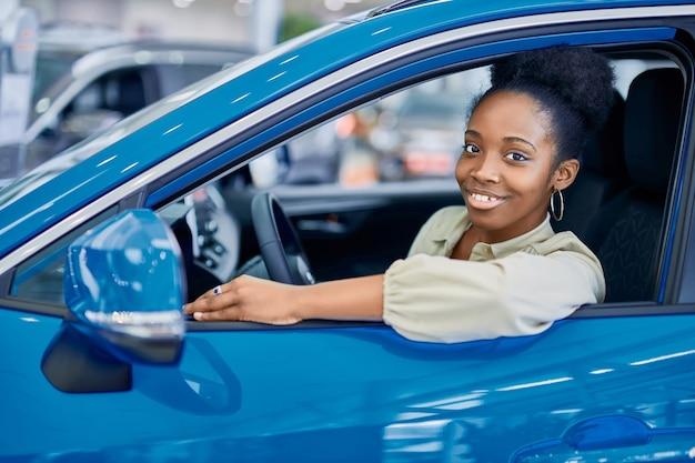 車のショールームで表される青い自動車のハンドルの後ろに満足しているアフリカの女性 Premium写真
