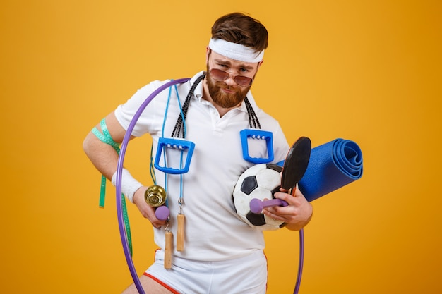 Satisfied bearded fitness man in sunglasses holding sports equipment Free Photo