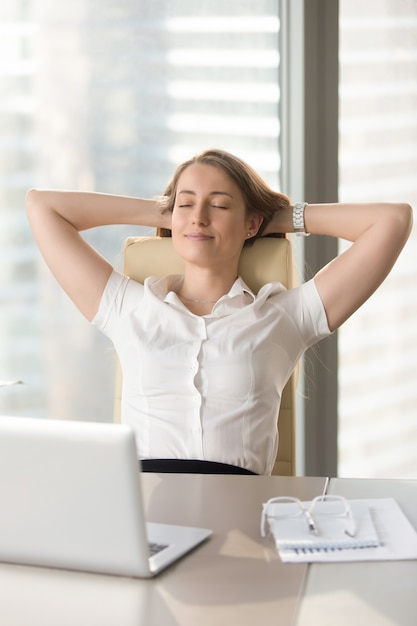 Satisfied businesswoman leaning back in chair Free Photo
