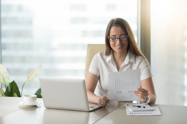 Satisfied businesswoman revising financial results Free Photo