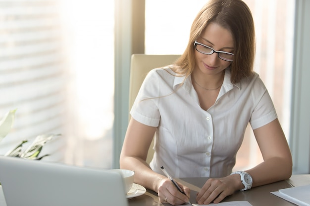 Satisfied businesswoman signs a contract at desk Free Photo