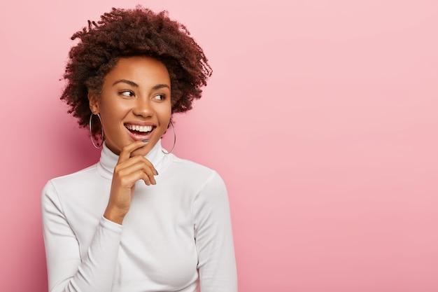 Modello femminile spensierato soddisfatto sorride dolcemente, tocca il mento, guarda da parte, nota una scena divertente, ride di qualcosa, ha i capelli scuri ricci naturali, vestito casualmente, isolato sul muro rosa Foto Gratuite